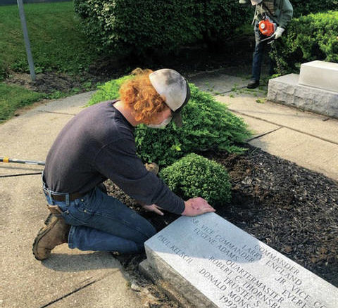 Robert Cracraft, a junior at BCHS, cleans the stone in front of the VFW, while Gavin Hitch, a junior at BCHS, trims bushes.