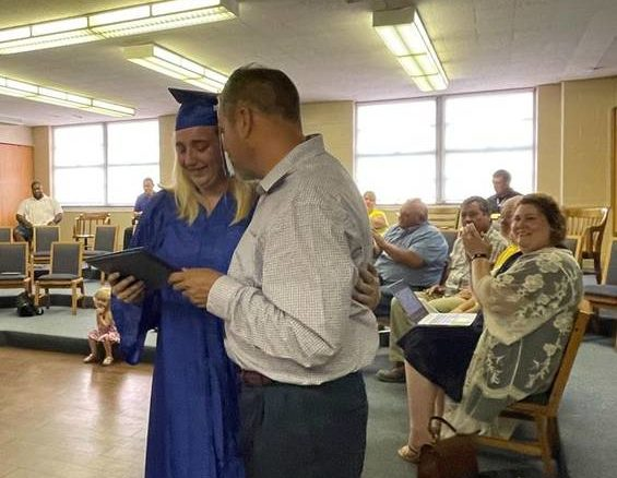 Mae-Kayla Linville receives her high school diploma during the Monday board of education meeting.