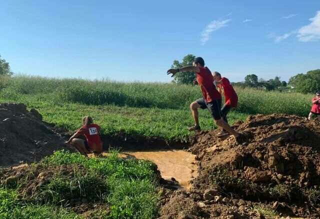 Competitors take a leap of faith during Saturday's Filthy 5K at Ford Acres Farm. All proceeds from the vent benefit A League of Their Own.