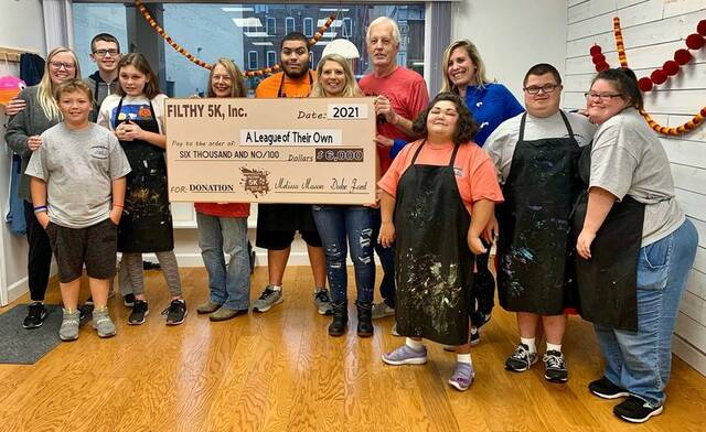 Duke Ford, center, one of the organizers of the Filthy 5K, was on hand recently to present proceeds from the event to A League of Their Own.