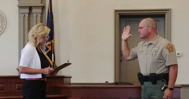 Robertson County Judge-Executive Stephanie Holbrook swears Terry Gray into office as Robertson County sheriff.